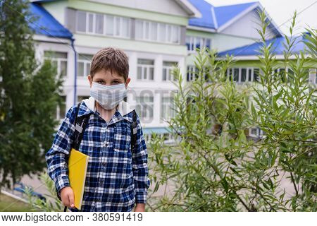 Child Boy With Bag, Mask And Book Stays Near Elementary School And Looks To The Camera