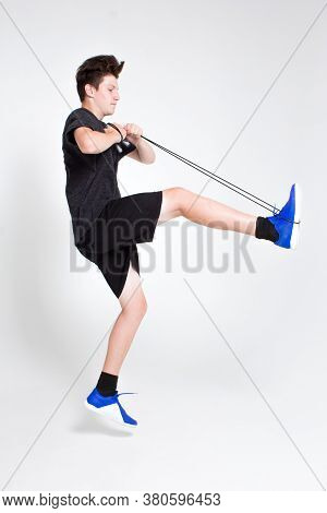A Young Man In A Black Sports T-shirt And Shorts, Blue Sneakers, Trains With A Jump Rope