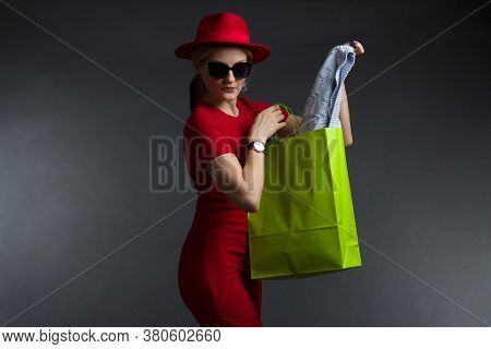 A Blonde In A Red Dress And Sunglasses Poses On A Dark Studio Background
