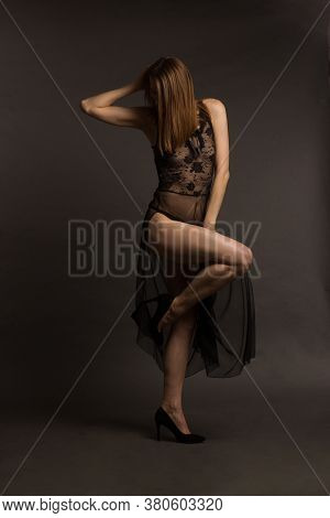 A Brunette In Lingerie And A Transparent Dress, Dancing On A Gray Studio Background.