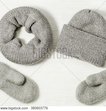 Knitted Grey Mittens, Hat And Scarf On White Wood Background. Fashionable Warm Clothes. Flat Lay. To