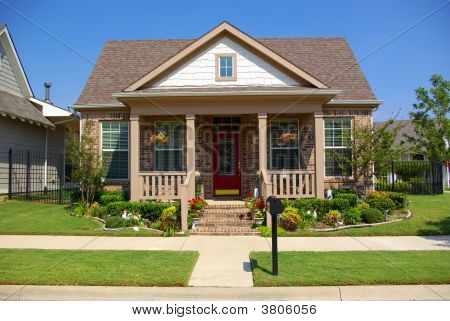 Idealistic single family American home. Front patio yard features green grass shrubs and flowers a walkway leading to entrance with blue sky in back ground. poster