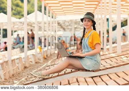 Portrait Of Young Smiling Woman Is Sitting On A Chaise Longue With A Laptop And Smiling. Beach Umbre