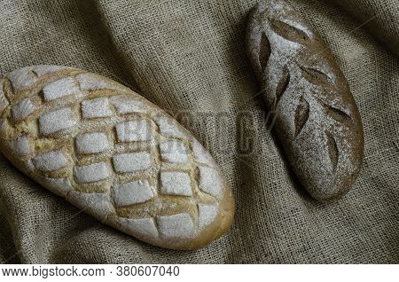 Family Business Baking Homemade Bread Background. Two Loaves Of Craft Bread On Burlap. Close-up Of T