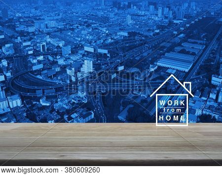 Work From Home Flat Icon On Wooden Table Over Modern City Tower, Street, Expressway And Skyscraper,