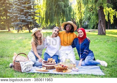Young Multiracial Women Are On Picnic In The Park. Best Multiracial Friends Have Fun Together.