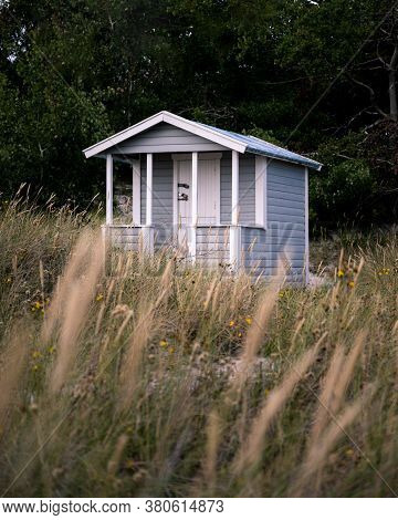 A Blue Abandoned Beach Hut In The Tall Grass On The Beach In The Village Falsterbo, Sweden