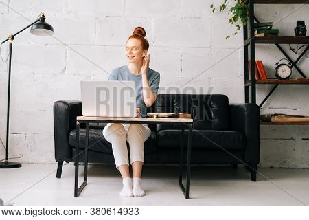 Cheerful Carefree Redhead Young Woman Listening Music In Wireless Earphones At Home Office At The Ta