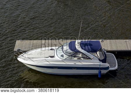 Pier Speedboat. A Marina Lot. Yacht Is Moored At The Quay. Marine Parking Of Modern Motor Boats. Rel