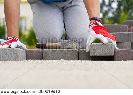 Worker Laying Paving Stones. Stone Pavement, Construction Worker Laying Cobblestone Rocks On Sand.