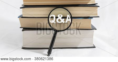 Q And A Text Inscription On Magnifying Loup With Stack Or Bunch Of Books On White Background, Search