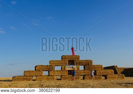 Ukraine, Kharkiv Region, Field, August 08, 2020 A Girl In A Red Dress On Top Of A Pyramid Of Straw B