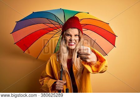 Young beautiful blonde woman wearing raincoat and wool cap holding colorful umbrella annoyed and frustrated shouting with anger, crazy and yelling with raised hand, anger concept