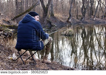 Fishing Rod In The Hands Of A Fisherman On The Lake. A Young Guy Sits On A Chair With A Spinning Rod