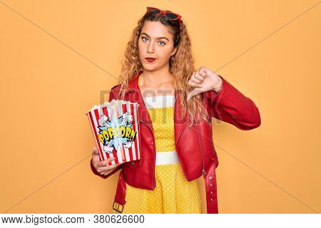Beautiful blonde woman with blue eyes eating salty popcorn snack over yellow background with angry face, negative sign showing dislike with thumbs down, rejection concept