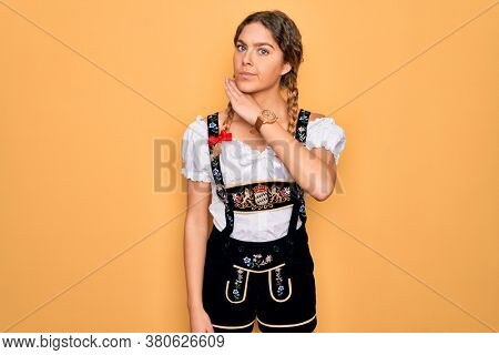 Young beautiful blonde german woman with blue eyes wearing traditional octoberfest dress cutting throat with hand as knife, threaten aggression with furious violence