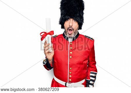 Middle age handsome wales guard man wearing traditional uniform holding diploma degree scared and amazed with open mouth for surprise, disbelief face