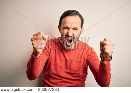 Middle age hoary man wearing casual orange sweater standing over isolated white background angry and mad raising fists frustrated and furious while shouting with anger. Rage and aggressive concept.