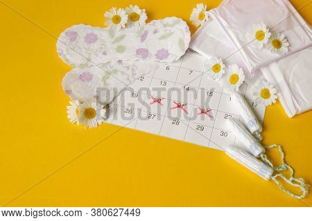 Menstrual Pads And Tampons On Menstruation Period Calendar With Chamomiles On Yellow Background. The