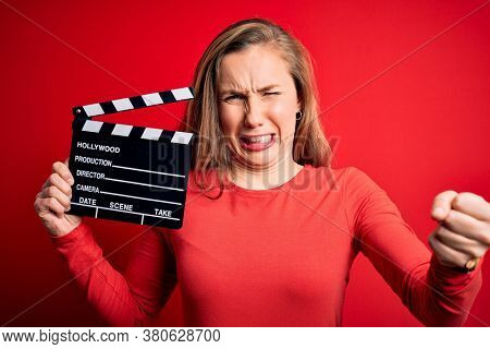 Young beautiful blonde clapper woman holding clapboard over isolated red background annoyed and frustrated shouting with anger, crazy and yelling with raised hand, anger concept