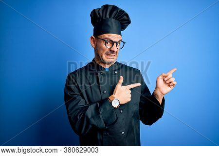 Young handsome chef man wearing cooker uniform and hat over isolated blue background Pointing aside worried and nervous with both hands, concerned and surprised expression