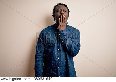 Young handsome african american man wearing casual shirt standing over white background bored yawning tired covering mouth with hand. Restless and sleepiness.