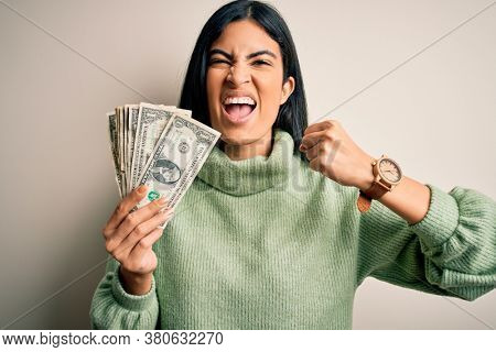 Young beautiful hispanic woman holding a pack of one dollar bunch of dollars annoyed and frustrated shouting with anger, crazy and yelling with raised hand, anger concept