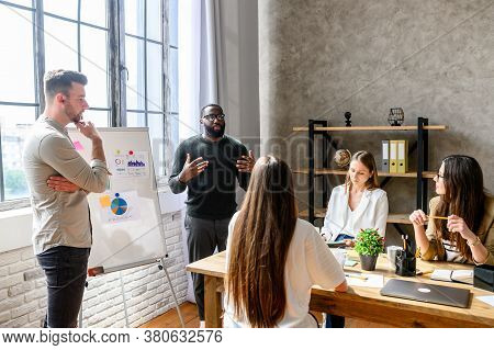 A Team Of Young And Successful Employees Listen To Progress Report From Male Afro-american Employee