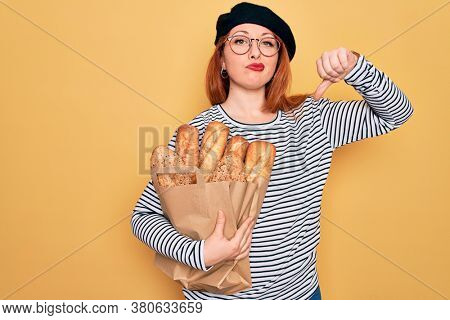 Young redhead woman wearing beret holding paper bag with bread over yellow background with angry face, negative sign showing dislike with thumbs down, rejection concept