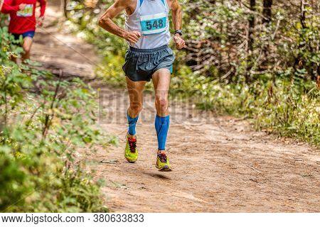 Man Athlete In Compression Sleeveless Socks Running Forest Trail Marathon