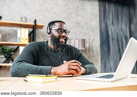 Young African-american Guy Is Call Center Worker Or Support. Smart Black Man In Eyeglasses Uses A Ha