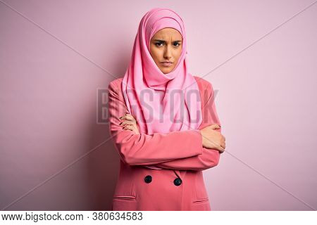 Young beautiful brunette businesswoman wearing pink muslim hijab and business jacket skeptic and nervous, disapproving expression on face with crossed arms. Negative person.