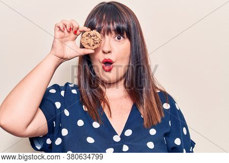 Young plus size woman holding chocolate cookie scared and amazed with open mouth for surprise, disbelief face