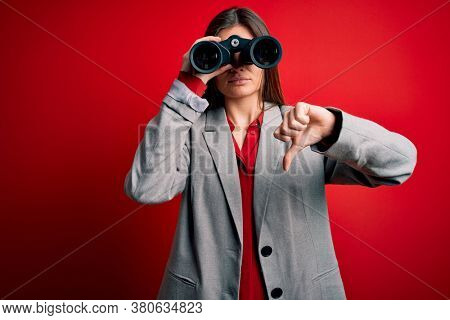 Young beautiful woman with blue eyes using binoculars over isolated red background with angry face, negative sign showing dislike with thumbs down, rejection concept