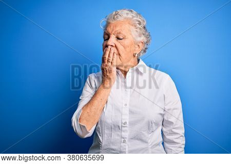 Senior beautiful woman wearing elegant shirt standing over isolated blue background bored yawning tired covering mouth with hand. Restless and sleepiness.