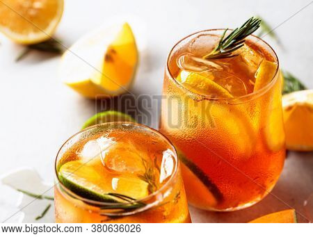 Iced Tea With Lemon, Lime And Ice Garnished With Rosemary Twigs. Selective Focus.