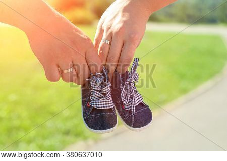 Parents-to-be Couple Holding Cute Blue Baby Shoes For Their Unborn Child. Happy And Healthy Pregnanc