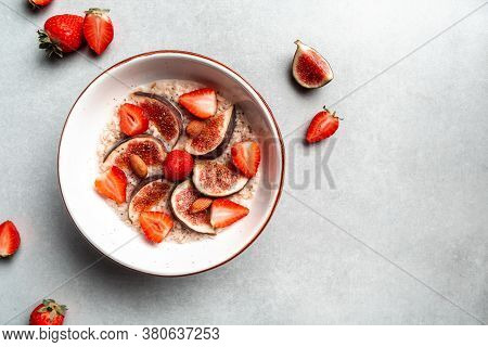 Oatmeal In A Plate With Fresh Figs, Almonds And Strawberries. Oatmeal With Fruits. Healthy Breakfast
