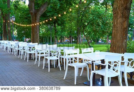 open air street cafe outdoor - white chairs and tables, decorated with illumination, the city Park and walking people