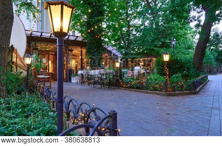 restaurant and beautiful architecture in the evening with street lights, open air street cafe outdoor, decorated with illumination, city Park and walking people