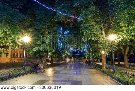 night view of Primorsky boulevard in Odessa city, Ukraine. Beautiful city Park and street illumination, walking people
