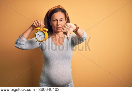 Middle age pregnant woman expecting baby at aged pregnancy holding alarm clock with angry face, negative sign showing dislike with thumbs down, rejection concept