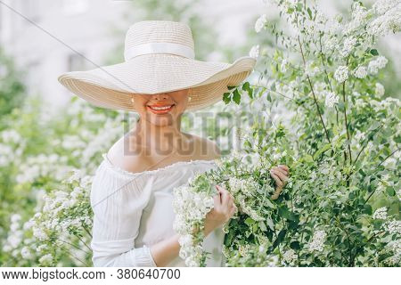 Spring Beauty. Elegant Woman Fashion Model With Flowers Outdoors