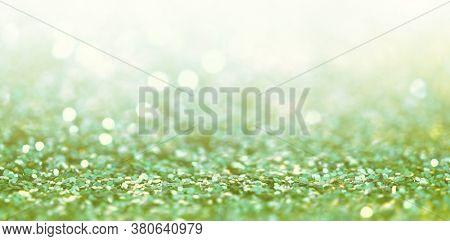 Defocus Abstract light blur blink sparkle horizontal backgound. Green glitter shine dots confetti.