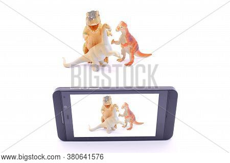 Dinosaur Toys Are Photographed On A Smartphone On A White Background