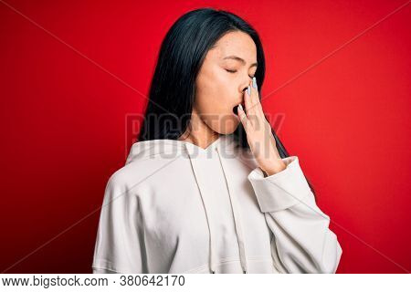Young beautiful chinese sporty woman wearing sweatshirt over isolated red background bored yawning tired covering mouth with hand. Restless and sleepiness.