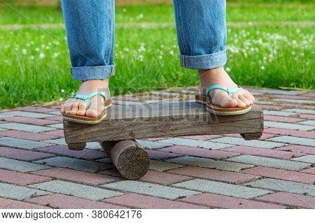 Bare Feet In Slates And Jeans On A Makeshift Balance Board, Brick Walkway, Grass In The Background,