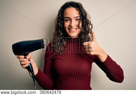 Young beautiful woman with curly hair using hair dryer over isolated white background happy with big smile doing ok sign, thumb up with fingers, excellent sign