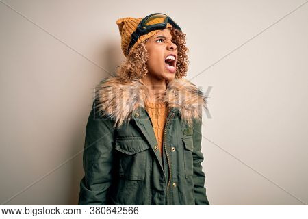 Young african american skier woman with curly hair wearing snow sportswear and ski goggles angry and mad screaming frustrated and furious, shouting with anger. Rage and aggressive concept.