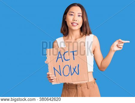 Young beautiful chinese girl holding act now banner smiling happy pointing with hand and finger to the side
